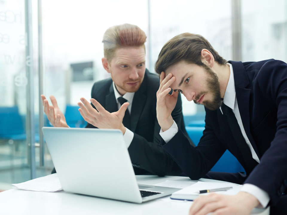 2 sales guys looking at a laptop